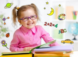 Happy child in glasses reading book. Early education concept.